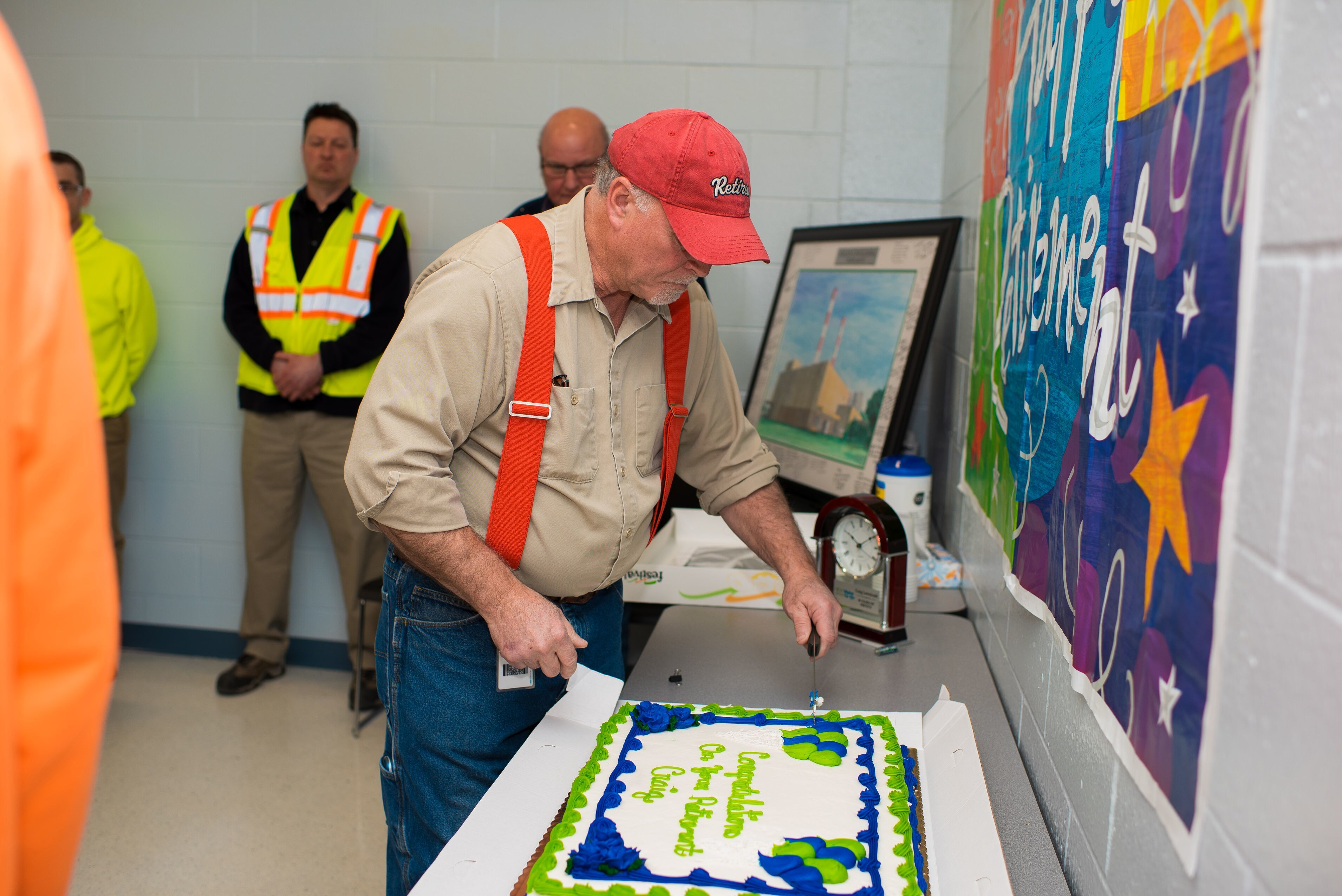 Craig Lawniczak cutting the cake at his retirement party.