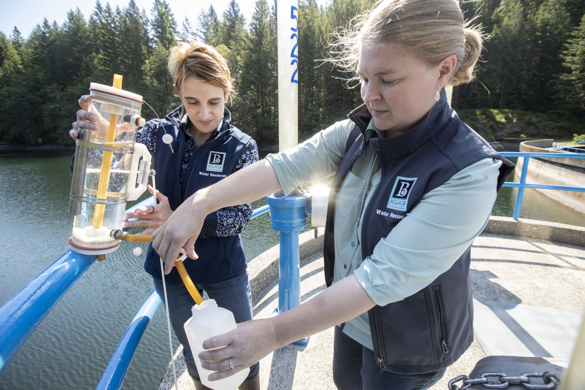 City of Bremerton Water Resources environmental technicians Lisa Campbell and Teresa Smith take a water sample from the Union River Reservoir. They're two of six women working in at the Bremerton facility. (PHOTO by Stephen Brashear)